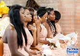 Bridesmaids sat on a pew in the church during a traditional Igbo wedding ceremony