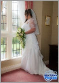 Full length shot of a bride in her white dress looking out of the window
