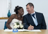 Igbo bride gazes into the eyes of her new husband whilst signing the register
