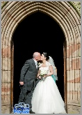Bride and groom kissing by the large gothic style door of an old church
