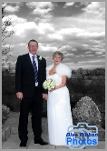 Middle aged wedding couple in colour with a B & W background with dramatic skyscape